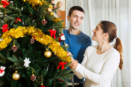 home decorating: Smiling man and woman decorating Christmas tree in home interior