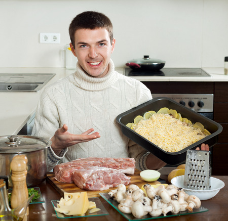 handsom: Young handsom man cooking french-style meat in the kitchen at home Stock Photo