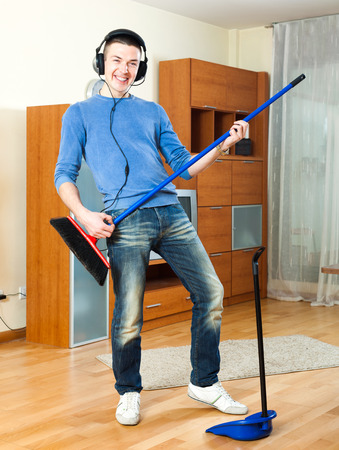 Cheerful hansome man  with dustpan and brush in living room