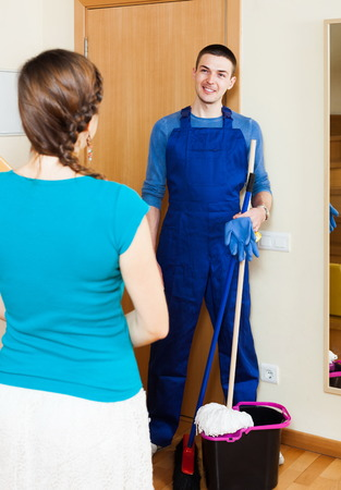 houseman: Housewife meeting smiling cleaner at the door at home