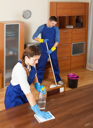 premises: Professional cleaners cleaning in living room
