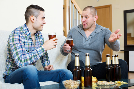 off day: adult men drink beer with a snack at home on a day off. Focus on the right man