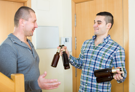 buddy: Guy meeting smiling buddy with beer bottles at doorway  in flat
