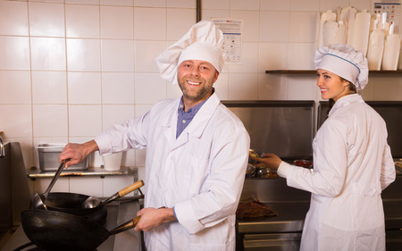 Positive smiling cooks working together at kitchen in take-away restaurant photo