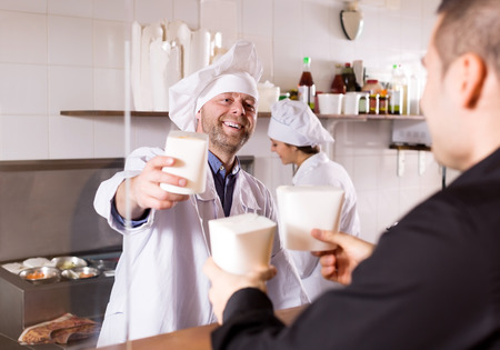 house robe: Smiling adult cook and client buying take-away food at eating house