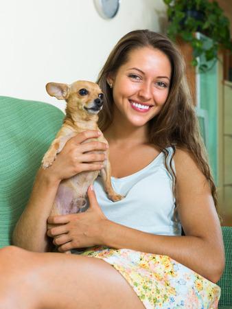 russkiy: Happy smiling girl holding Russkiy Toy Terrier indoor Stock Photo
