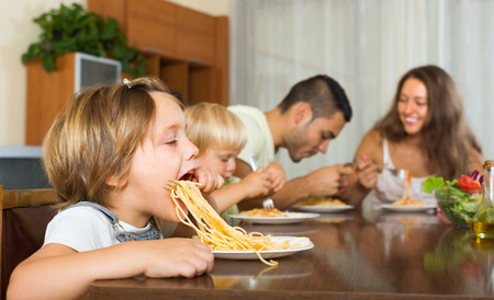 gladful: Positive family of four having lunch with spaghetti at home