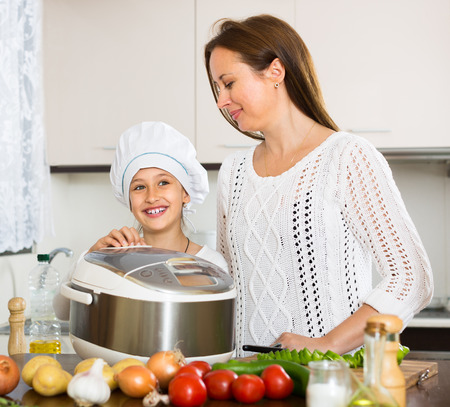 Happy european mother and little daughter using multicooker at kitchen photo