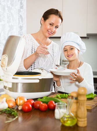 slow cooker: Slow cooker helping mother and girl to prepare dinner at home
