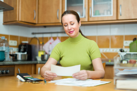 Orderly female with money and invoices for payment indoors photo