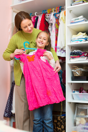 style advice: Happy smiling preschooler girl with mom choosing apparel in cloakroom