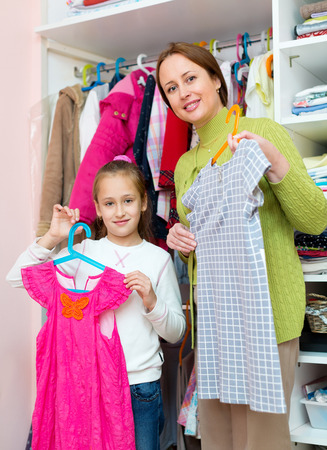 30 to 35: Young mother and daughter staying near wardrobe with dresses on hangers.