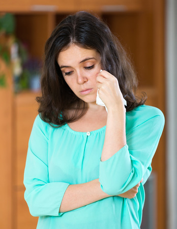 singleness: Young brunette woman crying at home wiping away tears with a handkerchief