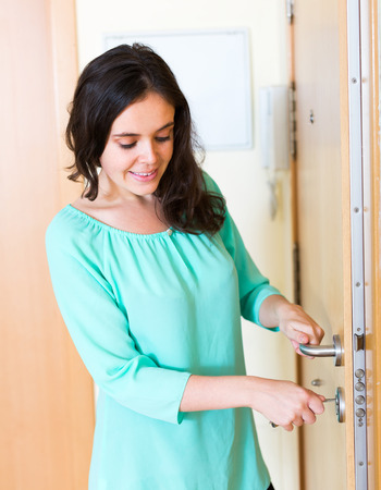 door opening: Young adult brunette unlocking outer door and smiling Stock Photo