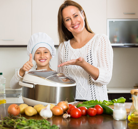 Slow cooker helping mother and smiling girl to prepare dinner at home kitchen photo