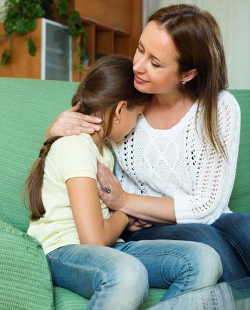 home comforts: Mother comforting crying little daughter at home Stock Photo