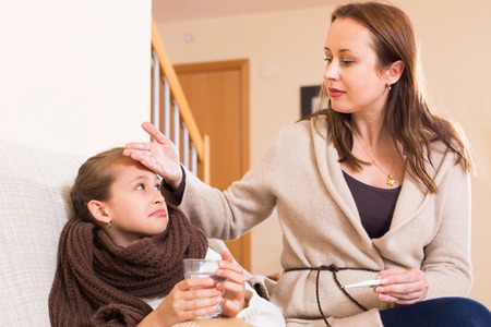 schooler: Woman caring for sick daughter who has high temperature in living room