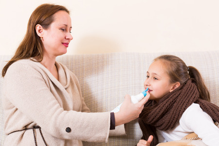 cold cure: Happy mother and schoolgirl daughter taking salt water cure for cold Stock Photo