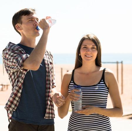 sediento: Pareja de j�venes sedientos de agua potable de la botella en el d�a soleado Foto de archivo