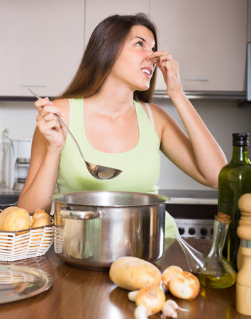 bad smell: Young woman pinched her nose avoiding bad smell from pan Stock Photo
