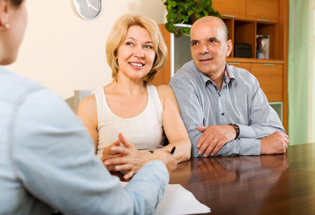 private insurance: Smiling  mature couple discussing details of private insurance with agent Stock Photo