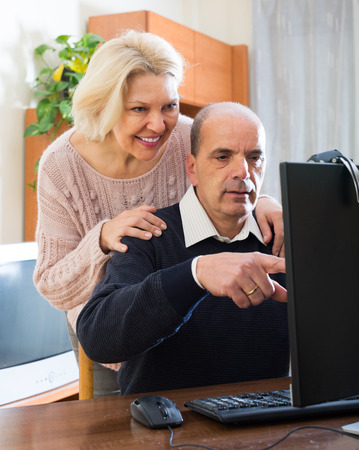 global retirement: Happy pensioners are talking on skype with their foreign friends indoor