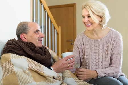 taking a wife: Sick aged man with cold taking pill from caring woman