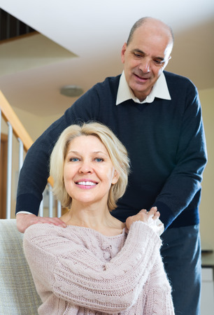 Portrait of senior smiling man giving tired wife a back massage photo