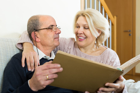 spouses: Portrait of loving senior spouses smiling with picture album indoors