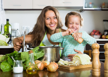 Happy young  family cooking soup  at home kitchen