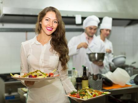 아름다운 카페에서 부엌에서 요리를 복용하는 여성 웨이터 미소