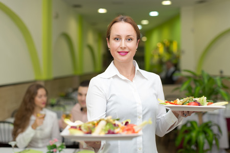 waiter serving: Smiling female waiter serving guests table in restaurant Stock Photo