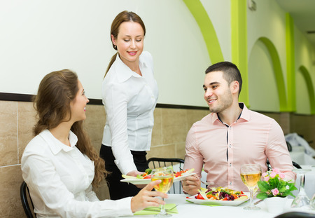 visitors: Smiling female waiter with plates serving visitors table in cafe