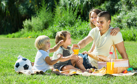 Happy parents with little girls having picnic at countryside