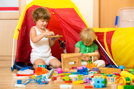 play blocks: Two  tranquil children playing with  toys in home interior Stock Photo
