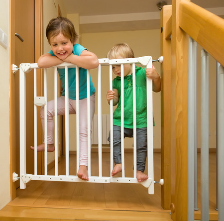Two baby girls approaching safety gate of  stairs Stock Photo