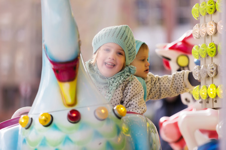 carrousel: Portrait of little sisters laughing at roundabout
