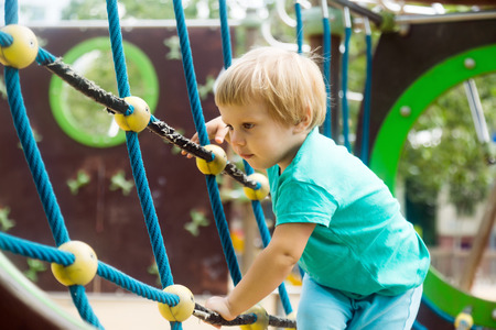 adroitness: little girl climbing the ropes of challenge net at playground Stock Photo