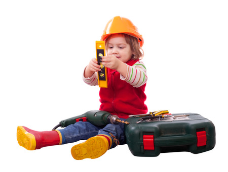 Child in builder hardhat with tools. Isolated over white  photo