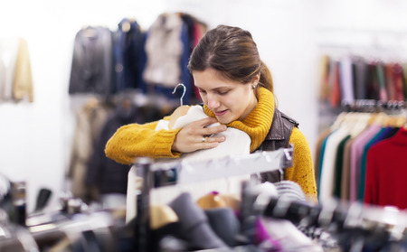 ordinary woman: Ordinary woman choosing sweater at clothing store