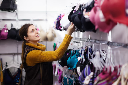 female buyer chooses bra at clothing store