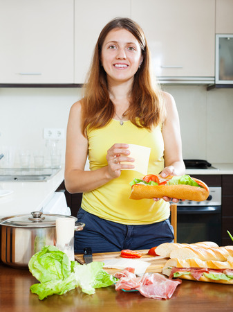 ordinary woman: Ordinary woman cooking spanish sandwiches (bocadillo) with cheese and  hamon in her kitchen