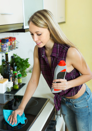 tidying up: Young blonde housewife tidying up kitchen-range after cooking and smiling