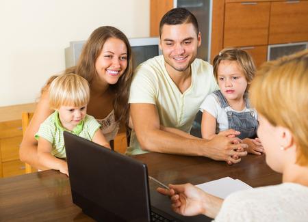 Los padres y dos hijas que se sientan delante de un trabajador social. Centrarse en la niña Foto de archivo - 36390928