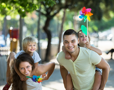 fun day: Happy little girls with windmills sitting on smiling parents arms outdoor Stock Photo