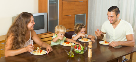 gladful: happy family of four  having lunch with macaroni and ketchup at home together