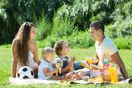sunny day: Feliz sonriente joven familia de cuatro que tienen comida campestre en el prado en d�a de verano