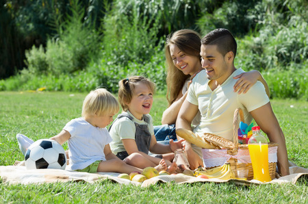 picnic food: Young parents with little daughters having holiday with picnicin in summer Stock Photo