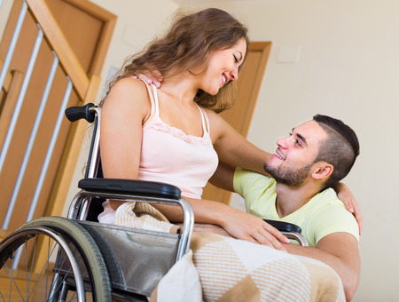 invalidity: Loving girl in wheelchair with her boyfriend indoor Stock Photo