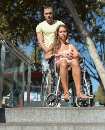 Young caregiver and girl in invalid chair near undercrossing